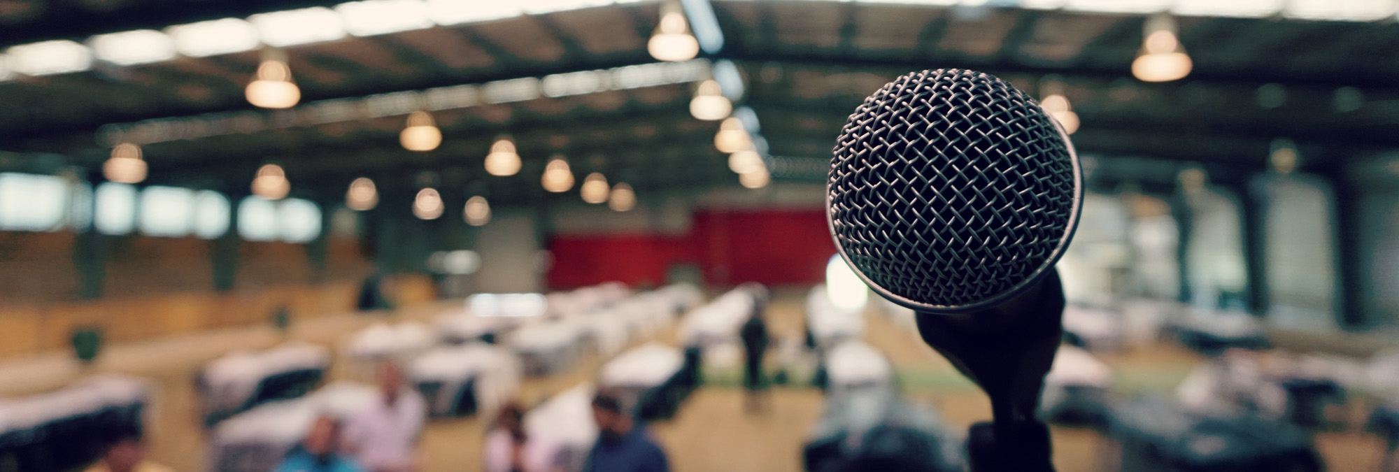 Image shows an up close shot of a microphone on stage during preparation of a big event