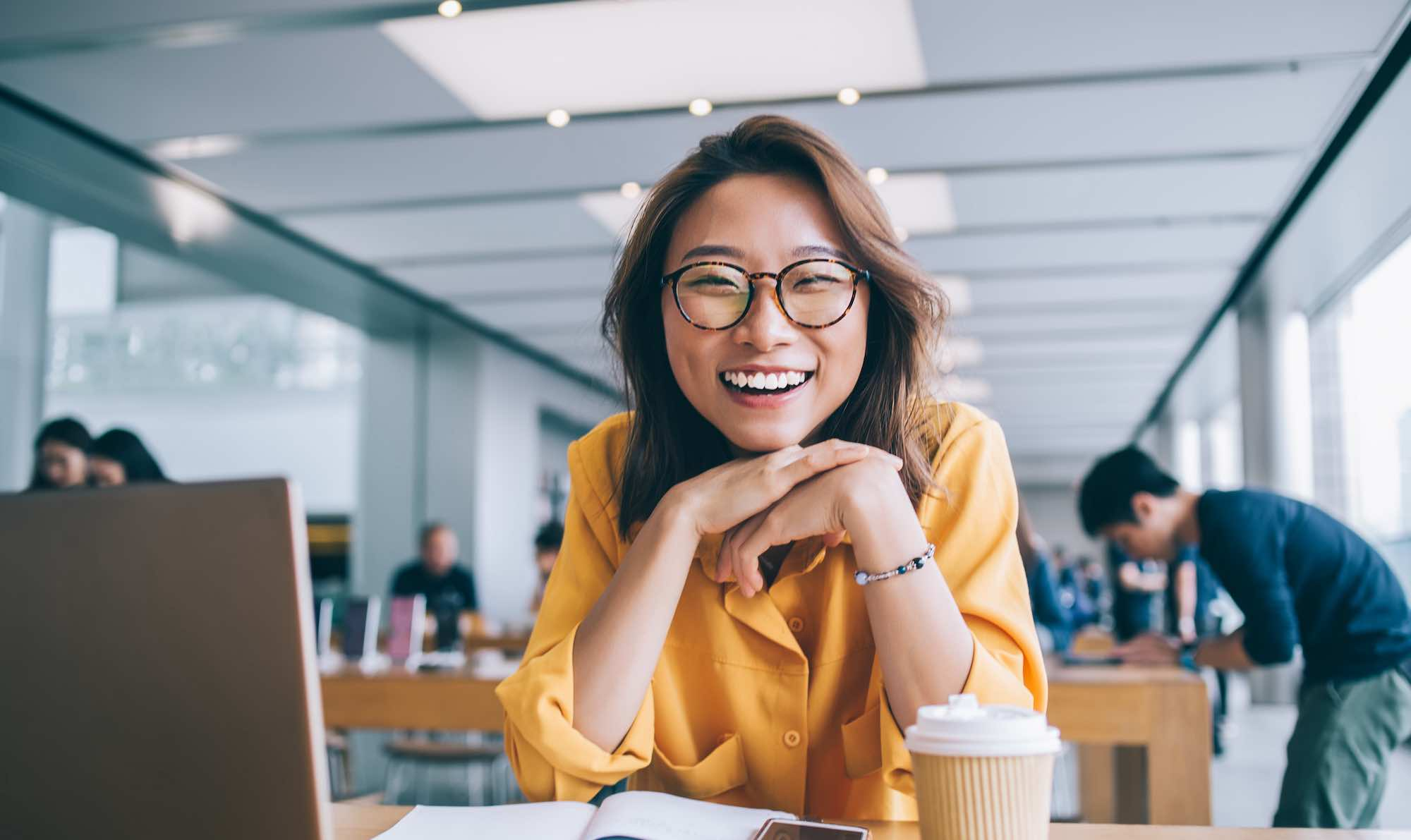 Image shows a happy smiling woman sitting at a table with a coffee and her digital devices to hand